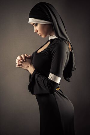 young nun in a black robe prays Standard-Bild