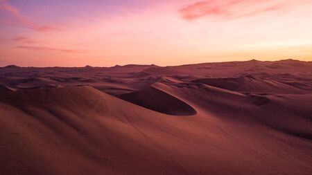 Aerial view of sand dunes during the sunset creating abstract shapes due to wind formations. Dreamy colors, martian landscape.