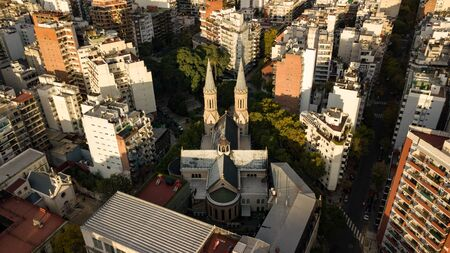 Aerial view of the catholic church in the middle of the Palermo neighborhood in Buenos Aires, Argentina. The ch surrounded by autumn trees during the sunset with warm light and visible surroundings.