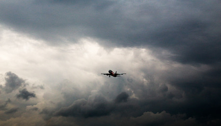 Aircraft flying in stormy Stock Photo
