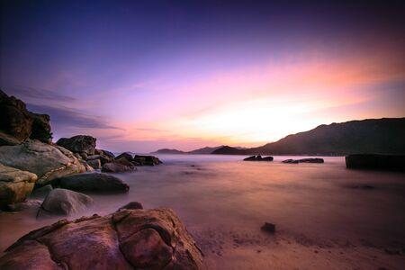 waves crashing: Waves crashing on rocky shore in sunset