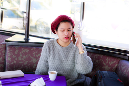 woman dialing phone number: Vietnam Da Lat city 12 months 2. 2015: beautiful Asian girl talking on the phone in a cafe in Da Lat Editorial