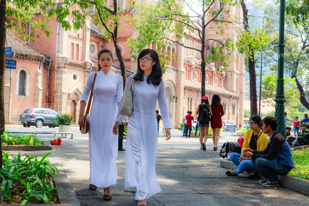 Hochiminh City Vietnam February 16: unidentified Vietnamese Ao dai girls wearing white on the street on February 16 2014. Ao dai is famous traditional for women in Vietnam Custume.