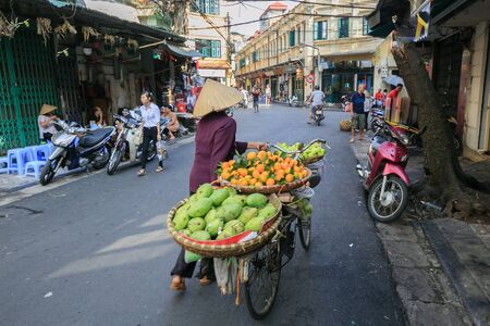 small town life: Vietnam Hanoi City October 29: Daily life of the fruit vendors sell on her bicycle in the typical old town street in Hanoi on October 30 2014 at city Vietnam.This market is small for retails and hawkers. Editorial