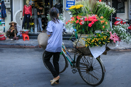 small town life: Vietnam Hanoi City October 29: Daily life of the fruit vendors sell on her bicycle in the typical street in old town Hanoi on October 30 2014 at city Vietnam.This market is small for retails and hawkers.
