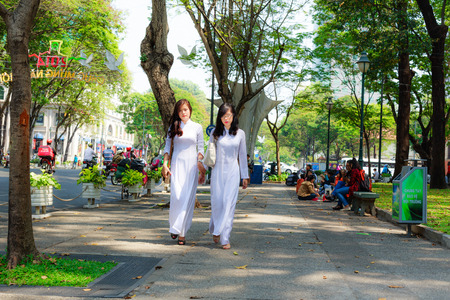 famous women: Hochiminh City Vietnam February 16: unidentified Vietnamese Ao dai girls wearing white on the street on February 16 2014. Ao dai is famous traditional for women in Vietnam Custume.