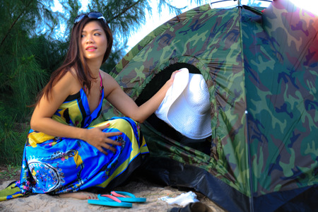tent city: Ho Coc Beach Vung Tau city Vietnam July 13 2014: Unknown a beautiful young girl sitting in front of his tent at campsite on the banks of Ho Coc Beach Vung Tau
