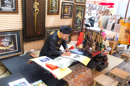 Ho Chi Minh City Vietnam January 20 2014: Vietnamese Lunar Year festival scholar at in calligraphy at the Youth Cultural House gi. This is a tradition of the Vietnamese lunar new year