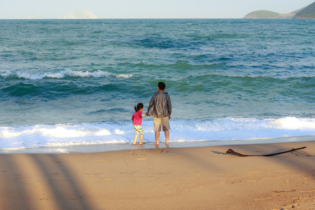 proved: Nha Trang city Vietnam January 27 2014: Unknown seafront promenade father and daughter proved to be extremely excited SHE enjoy the sea waves