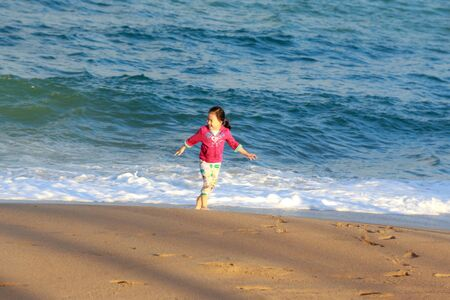proved: Nha Trang city Vietnam January 27 2014: Unknown Little cute girl running on the white sandy beach in Nha Trang Vietnam proved to be extremely excited SHE enjoy the sea waves