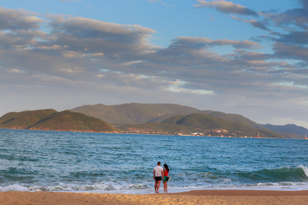 confide: Nha Trang Vietnam January 27 2014: Sunset on the beach in Nha Trang city a couple undefined stand to talk and confide on coast Editorial