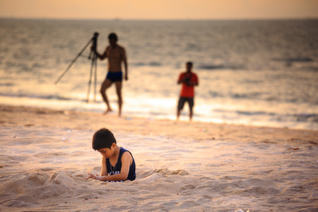 unknown men: Vung Tau Vietnam May 16 2015: a young boy Unknown sitting alone on the beach with sand vi thinking is far behind look like the two men holding the image capture device
