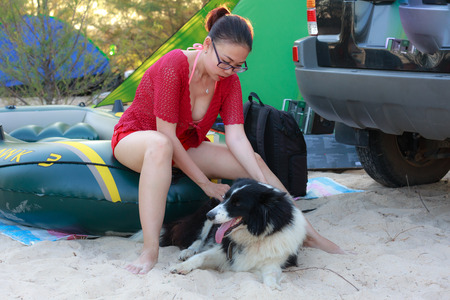 tent city: Vietnam Vung Tau city May 15 2015: Woman with pet dog inside the tent at the campground near the coast
