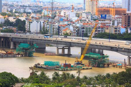 Ho Chi Minh City Vietnam May 24 2015: yellow crane is operating a building piers for subway route will pass through here parallel to the bridge Saigon