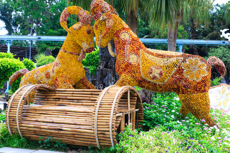 transplants: Ho Chi Minh City Vietnam April 11 2015: goat symbol of New Year pictures by the artist bending flowers and elaborately trimmed trees transplant for days