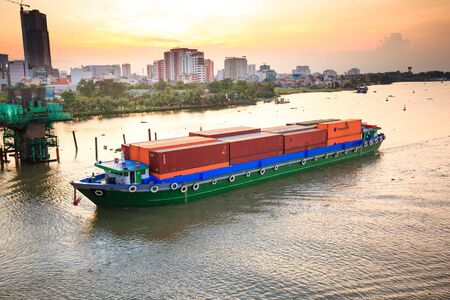 Hochiminhcity Vietnam June 3 2015: Maritime transport loading container on river water vessel on scene at riverside apartment residential and industrial city of Vietnam June 3 2015