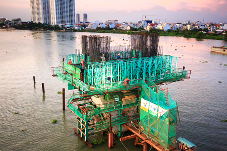 pilings: Hochiminh City Vietnam June 3 2014: the construction Workers steel and beton pier for metro lines crossing the Saigon River