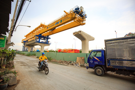 beton: Ho Chi Minh City Vietnam June 5 2014: Giant cranes are Preparing to take the beam beton built for subway lines cross the Saigon River Road