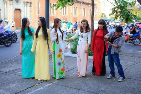 Vietnam Ho Chi Minh city April 3 2015: the young girls wear more clothing colorful dragon talking happily on a street in Ho Chi Minh city is a traditional dress costume the women Vietnam