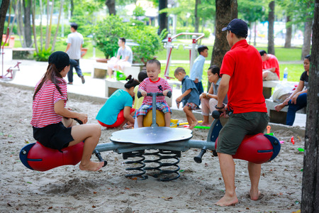 turnabout: Hochiminh City, Vietnam - June 21, 2015: Unknown, parents playing with baby in the park in the city HoChiMinh, Vietnam