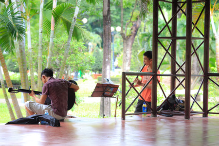 two boys: Hochiminh City, Vietnam - June 21, 2015: undefined, two boys playing guitar and flute l in a park in Ho Chi Minh City, Vietnam Editorial