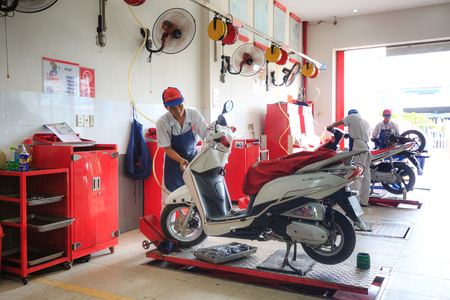 tinkering: Hochiminh City, Vietnam - June 23, 2015: Professional motorcycle repairman at a service center of Honda motorcycles in Ho Chi Minh City, Vietnam Editorial