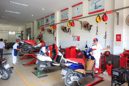 tinkering: Hochiminh City, Vietnam - June 23, 2015: professional motorcycle repairman at a service center of Honda motorcycles in Ho Chi Minh City, Vietnam
