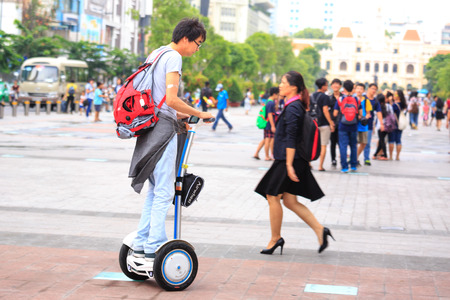 Hochiminh City, Vietnam - July 8, 2015: Man riding a Segway electric vehicle two wheels on a young tour sightseeing gyropode on Walking Street Nguyen Hue Street, HoChiMinh city center