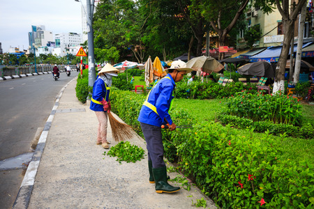 green clothes: Hochiminh City, Vietnam - August 8, 2015: Unidentifield. Workers are pruning off branches environment of scrubs in a neighborhood in HoChiMinh city. a normal job but the significant Editorial