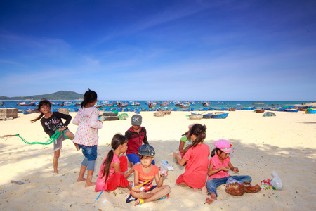 kids jumping: Phuyen province, Vietnam - August 16, 2015: Unknown children playing together of a fishing village on the beach, while parents are working at sea chng
