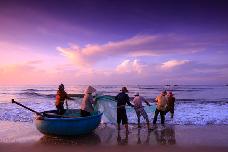 Strand Lagi, Binh Thuan provincie, Vietnam - 29 augustus 2015: Onbekend Vissers die trek e zijn de visnetten khi zonsopgang. Dit is vragen voor hun dagelijks werk Stockfoto - 45210990