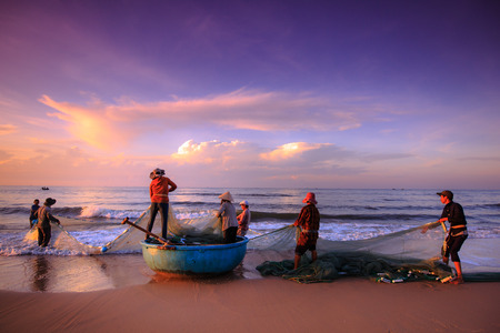 fisherman: Beach Lagi, Binh Thuan province, Vietnam - August 29, 2015: Unknown Fishermen who pull up th are the fishing nets khi sunrise. This is ask for their daily work