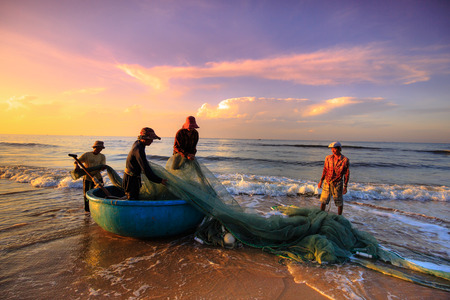 pull up: Beach Lagi, Binh Thuan province, Vietnam - August 29, 2015: Unknown Fishermen who pull up th are the fishing nets khi sunrise. This is ask for their daily work