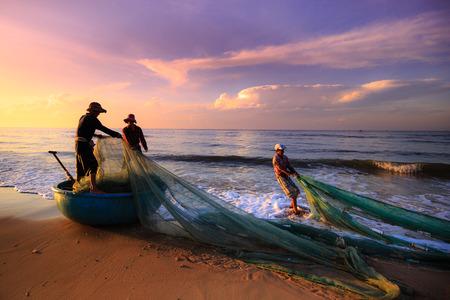 Strand Lagi, Binh Thuan provincie, Vietnam - 29 augustus 2015: Onbekend Vissers die trek e zijn de visnetten khi zonsopgang. Dit is vragen voor hun dagelijks werk Stockfoto - 45210997