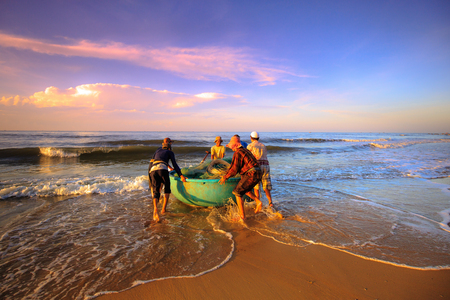 Beach Lagi, Binh Thuan province, Vietnam - August 29, 2015: Unknown Fishermen Were Carrying th push the boat fishing nets to trawling in the early morning sunlight. This is ask for their daily work Editorial