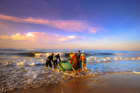 work boat: Beach Lagi, Binh Thuan province, Vietnam - August 29, 2015: Unknown Fishermen Were Carrying th push the boat fishing nets to trawling in the early morning sunlight. This is ask for their daily work Editorial