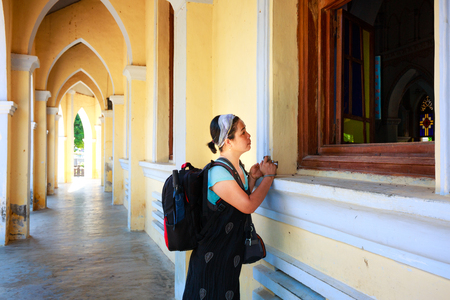 curiously: Phu Yen Province, Vietnam - August 16, 2015: Unknown woman was standing in the corridor of the Church and curiously watched the scene inside