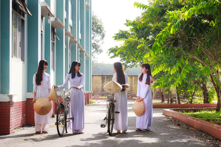conical hat: Hochiminh City, Vietnam - September 13, 2015: Unidentified Vietnamese Ao dai girls wear white uniform at c schoolyard. Ao dai is famous for traditional Custume woman in Vietnam.