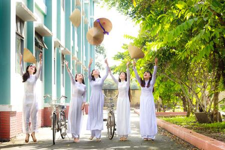 ao: Hochiminh City, Vietnam - September 13, 2015: Unidentified Vietnamese Ao dai girls wear white uniform at c schoolyard. Ao dai is famous for traditional Custume woman in Vietnam.