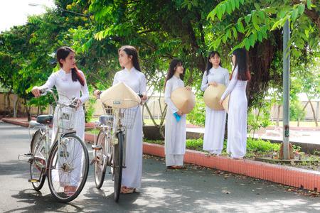 Hochiminh City, Vietnam - September 13, 2015: Unidentified Vietnamese Ao dai girls wear white uniform at c schoolyard. Ao dai is famous for traditional Custume woman in Vietnam.