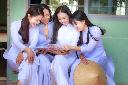 Hochiminh City, Vietnam - 13 september 2015: De niet geïdentificeerde Vietnamese Ao dai meisjes dragen witte uniform op c schoolplein. Ao dai is beroemd om de traditionele Custume vrouw in Vietnam. Redactioneel