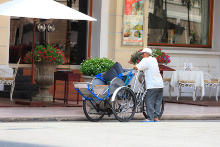 m hotel: Hochiminh City, Vietnam - September 20, 2015: an old cyclo rider was standing front of a luxury hotel printed with the hope tourists will use his m service