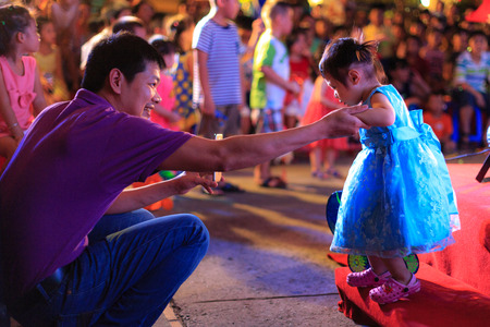 Hochiminh City, Vietnam - September 26, 2015: Children with Their parents are happy to attend mid-autumn festival at a residential building in the city of HoChiMinh. Mid-Autumn Festival is a celebration of the full moon in August every year in Vietnam
