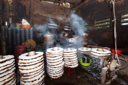 Provincia de Binh Thuan, Vietnam - 12 de octubre de 2015 a una pequeña fábrica, donde produce fideos de arroz, la mujer trae cesta llena de fideos de imprimir al vapor. Este es un trabajo duro para hacer un sabroso plato tradicional vietnamita Foto de archivo - 46584228