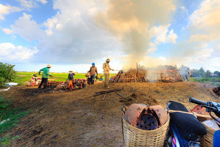 fling: Binh Thuan province, Vietnam - October 12, 2015 at Binh Duc traditional pottery village, the handicraftsmen burn products, ask for c m made by hands in the traditional way with wood and rice straw outdoors
