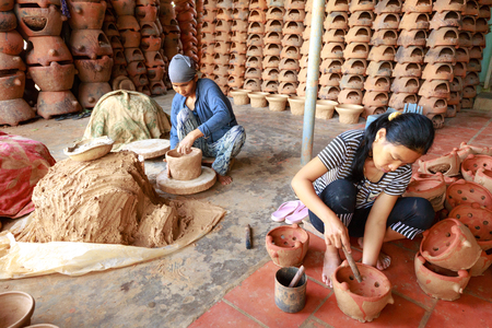 an operative: Binh Thuan province, Vietnam - October 12, 2015: A village potter creating in a new pot using traditional TECHNIQUES