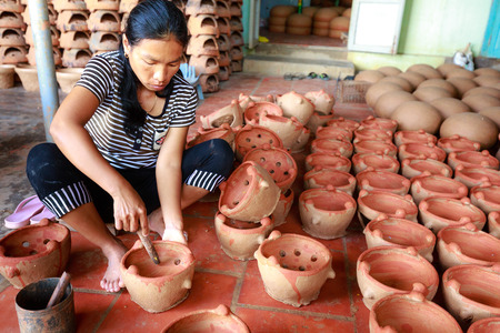 operative: Binh Thuan province, Vietnam - October 12, 2015: A village potter creating in a new pot using traditional TECHNIQUES