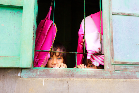 ojos tristes: Binh Thuan province, Vietnam - October 12, 2015 in a poor rural village, there are sad eyes of kids from window are expecting parents get home from work chng
