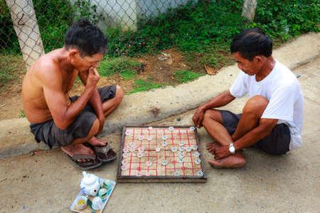 downloadable: Binh Thuan province, Vietnam - October 12, 2015: Two men are playing chinese print rural area on the sidewalk chess with a teapot