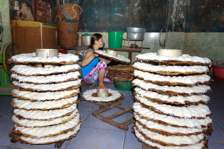 Binh Thuan province, Vietnam - October 12, 2015 at a small factory, where produces rice noodle, the woman Brings basket full of noodles print to the steamer. This is a hard work to make a very tasty traditional Vietnamese dish